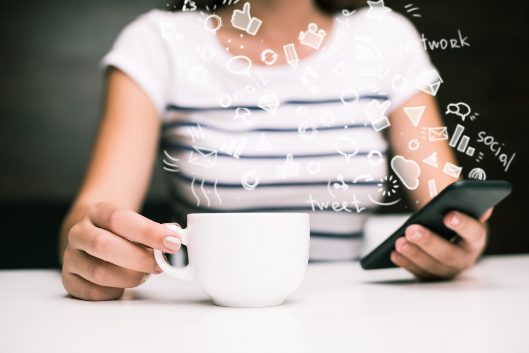 "Woman holding phone and coffee cup with words like ""social"", ""tweet"", and ""network"" coming from phone screen."